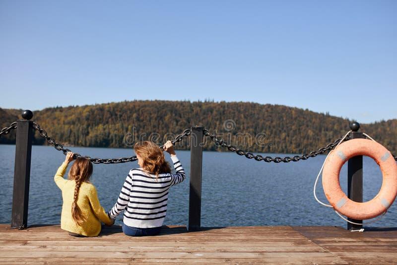 Mutter und Tochter der hinteren Ansicht, die am warmen Herbsttag des Piers sitzen lizenzfreie stockfotos