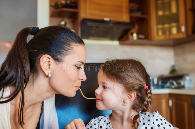Mutter und Tochter in der Küche, Spaghettis zusammen essend lizenzfreie stockbilder