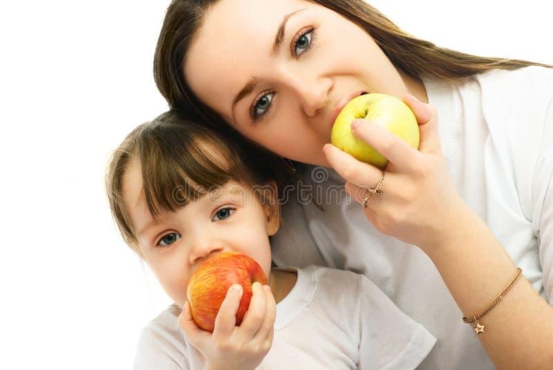 Mutter und Tochter, die Äpfel essen stockbilder