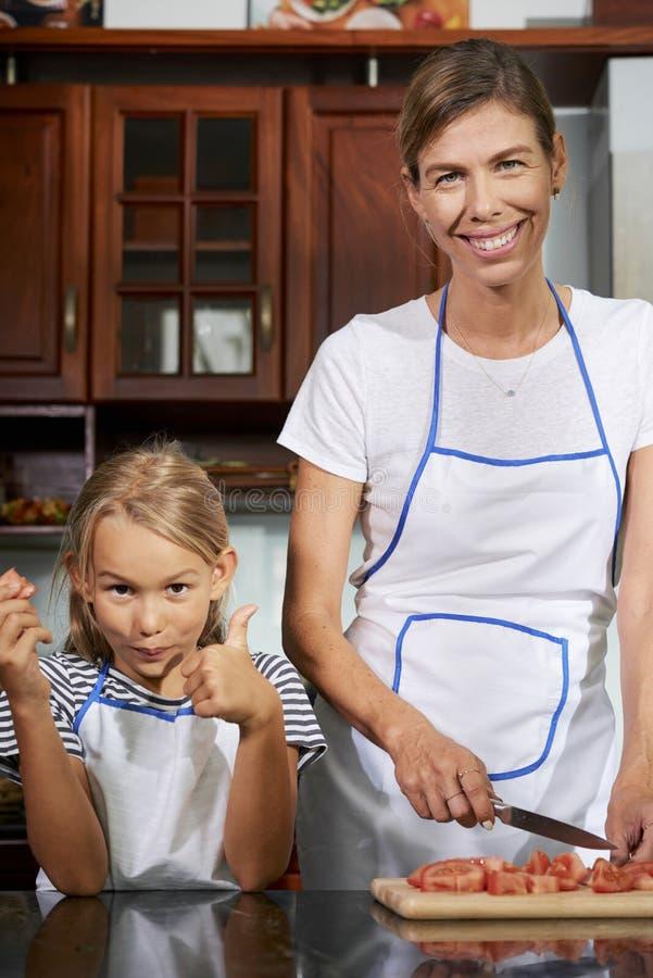 Mutter und Tochter, die Abendessen kochen lizenzfreie stockfotografie