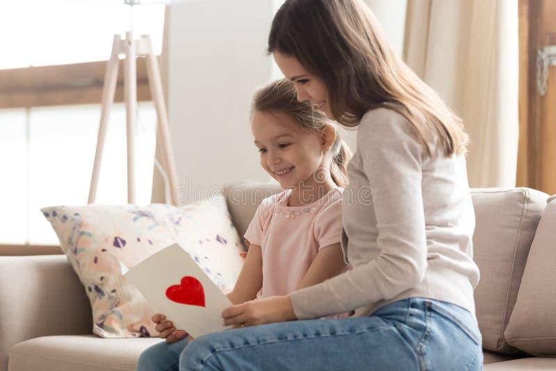 Mutter und Tochter, die auf Couchlesewünschen auf Postkarte sitzen stockbild