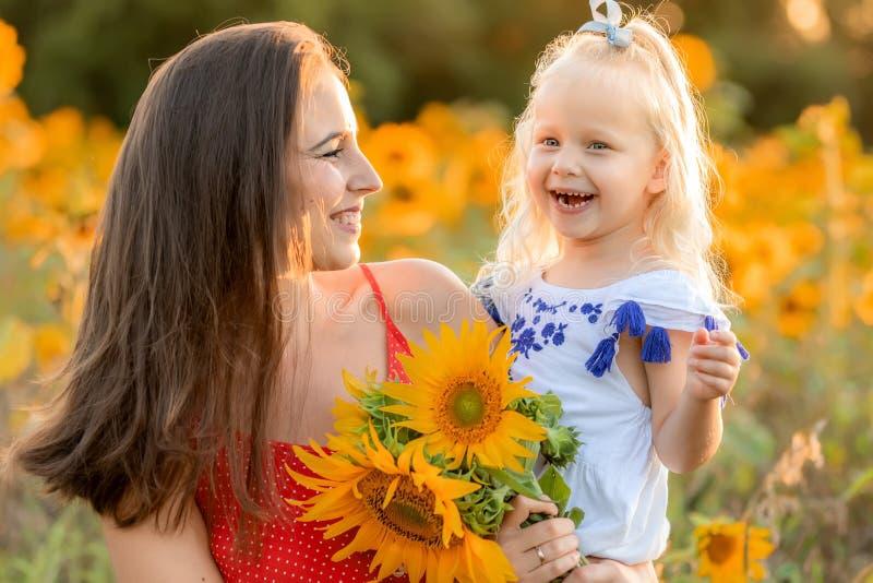 Mutter und Tochter, die auf dem Gebiet lachen stockbild