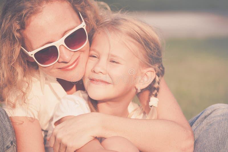 Mutter und Tochter, die auf dem Gras zur Tageszeit spielen lizenzfreies stockbild