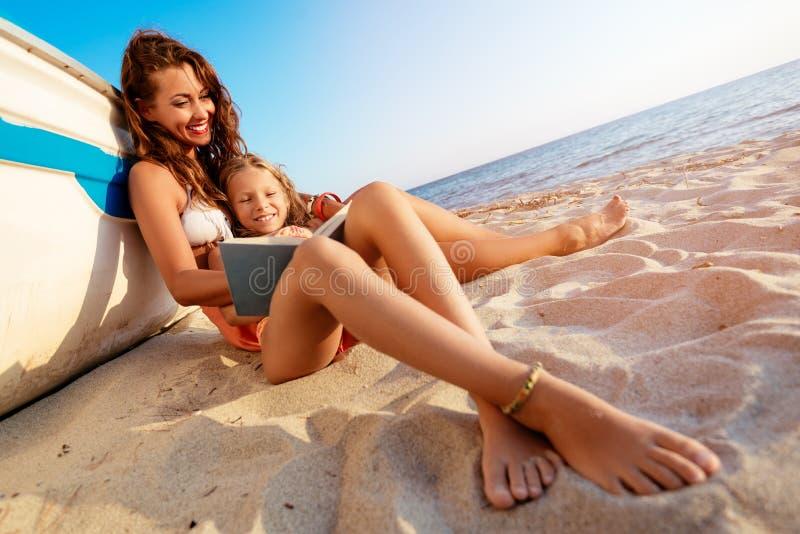 Mutter und Tochter, die auf dem Strand genießen stockbild