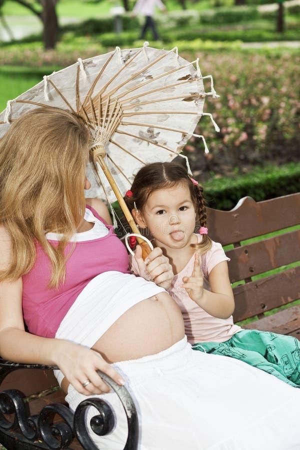 Mutter und Tochter, die auf einer Parkbank sitzen stockfotografie