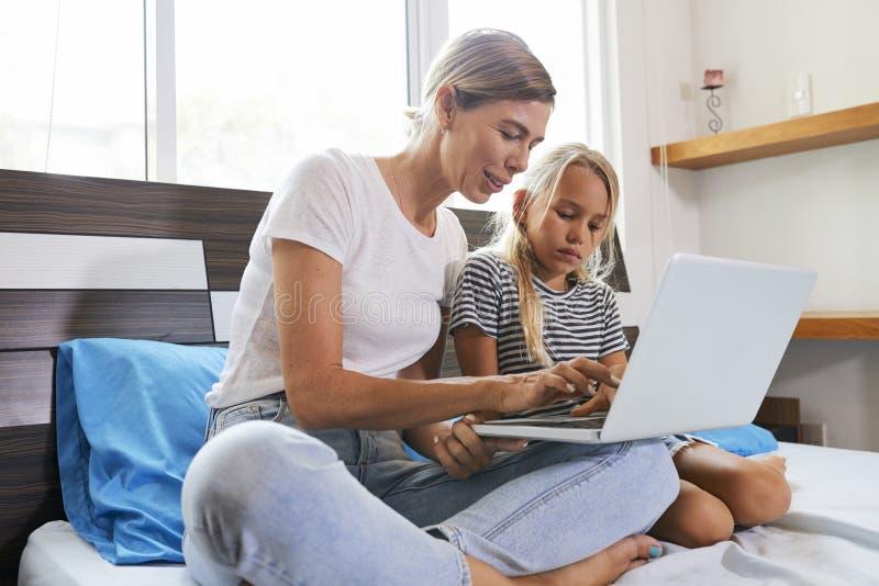 Mutter und Tochter, die auf Laptop spielen stockfotografie