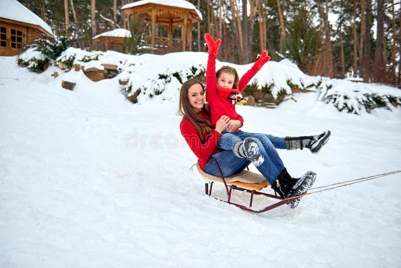 Mutter und Tochter, die auf Schnee im Wald rodeln lizenzfreies stockfoto