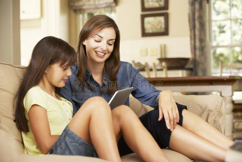 Mutter und Tochter, die auf Sofa At Home Using Tablet-Computer sitzen stockfoto
