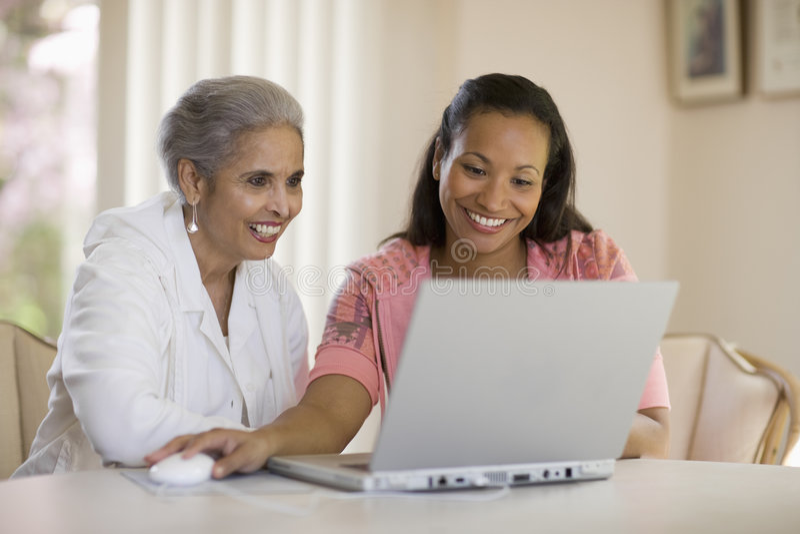 Mutter und Tochter, die Computer teilen stockfoto