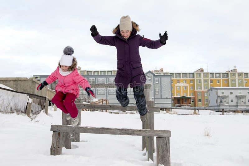 Mutter und Tochter, die in den Schnee springen lizenzfreie stockbilder