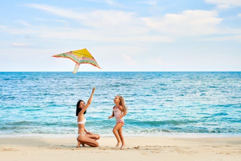 Mutter und Tochter, die den Spaß fliegt einen Drachen auf tropischem Strand hat lizenzfreie stockfotografie