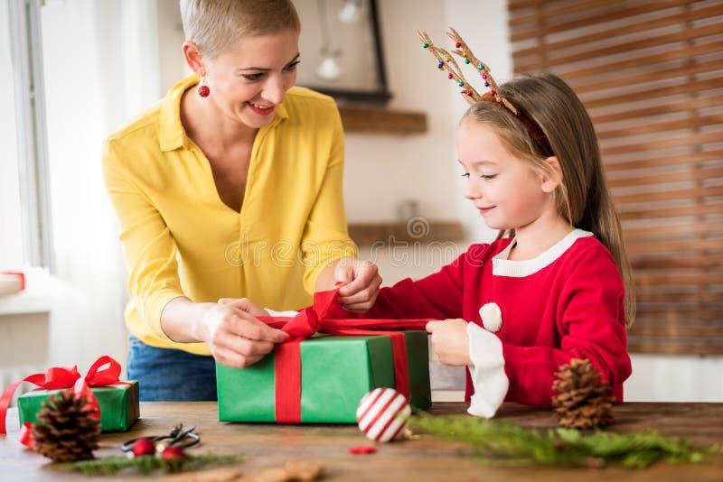 Mutter und Tochter, die den Spaß zusammen einwickelt Weihnachtsgeschenke im Wohnzimmer hat Offener Familienweihnachtszeitlebensst stockfotos