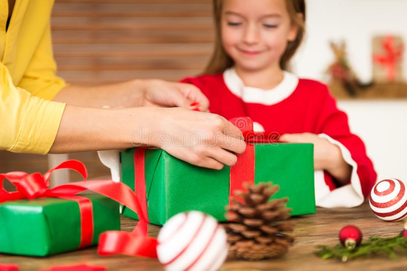 Mutter und Tochter, die den Spaß zusammen einwickelt Weihnachtsgeschenke im Wohnzimmer hat Offener Familienweihnachtszeitlebensst lizenzfreie stockfotos