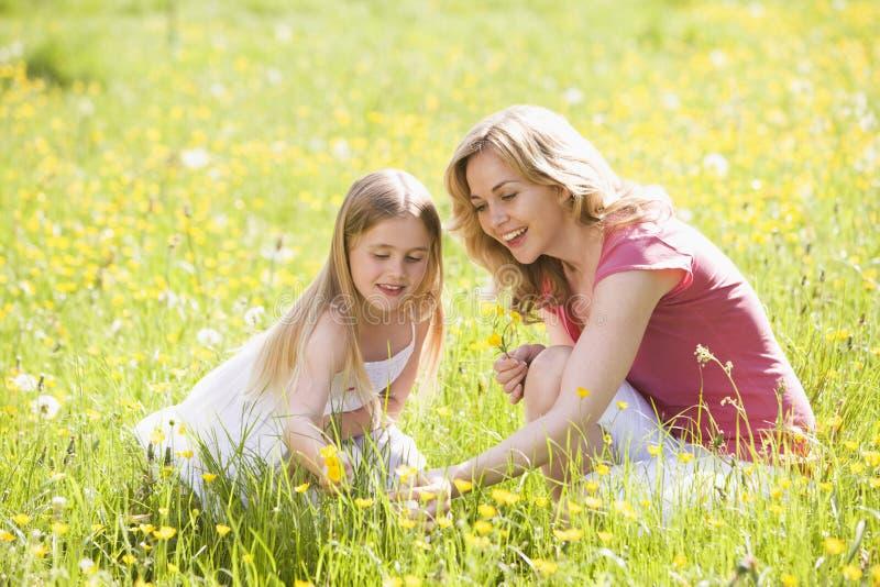 Mutter und Tochter, die draußen Blume anhalten lizenzfreies stockfoto