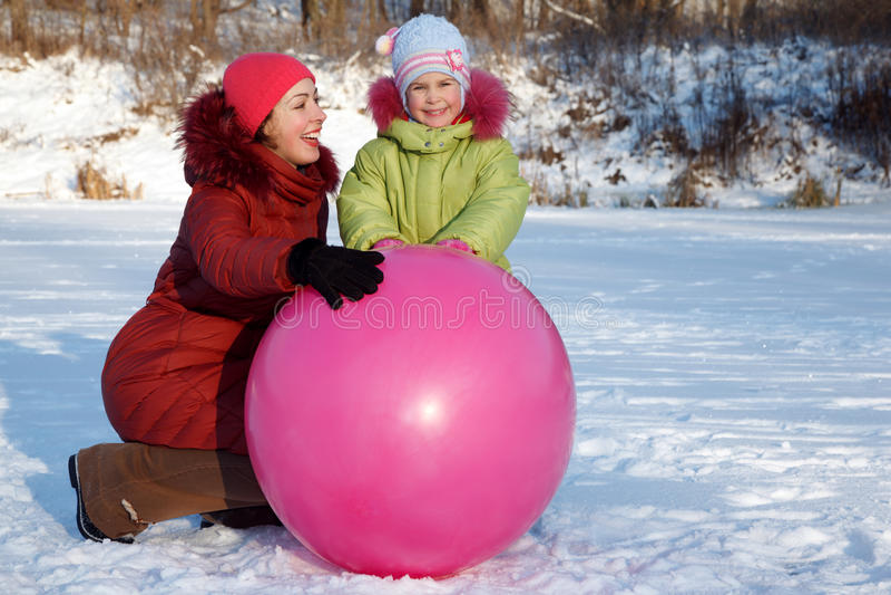 Mutter und Tochter, die draußen im Winter spielen stockfotografie