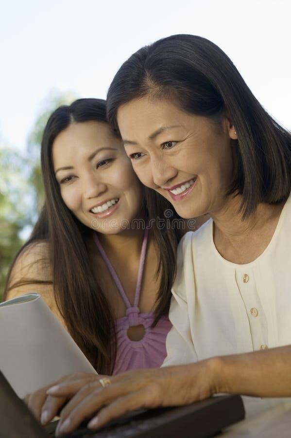 Mutter und Tochter, die draußen Laptop verwendet lizenzfreies stockbild