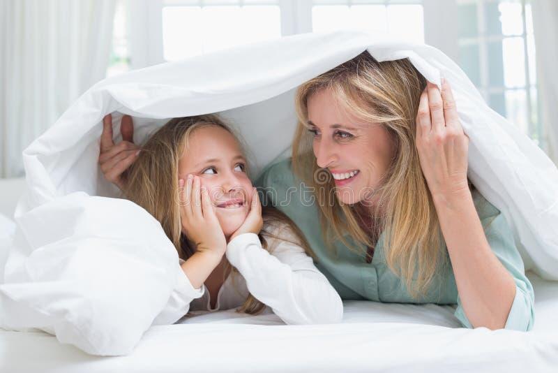 Mutter und Tochter, die einander unter der Daunendecke betrachten lizenzfreie stockfotografie