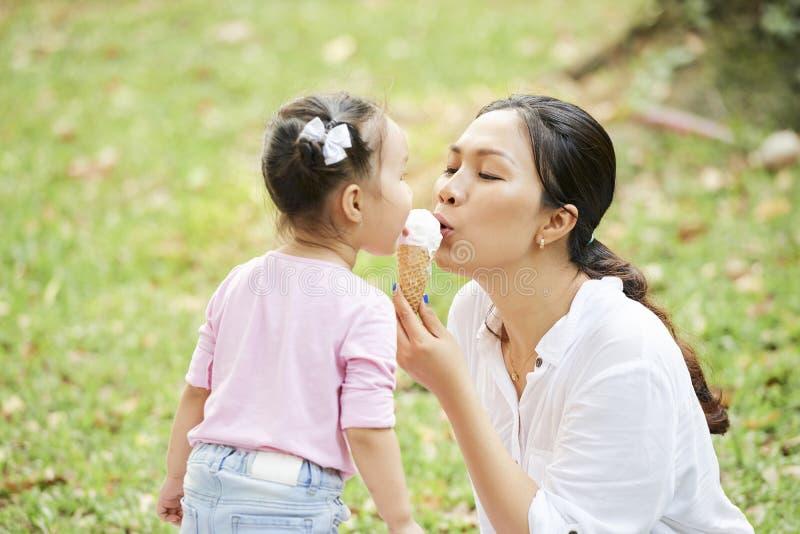 Mutter und Tochter, die Eiscreme essen stockfotografie