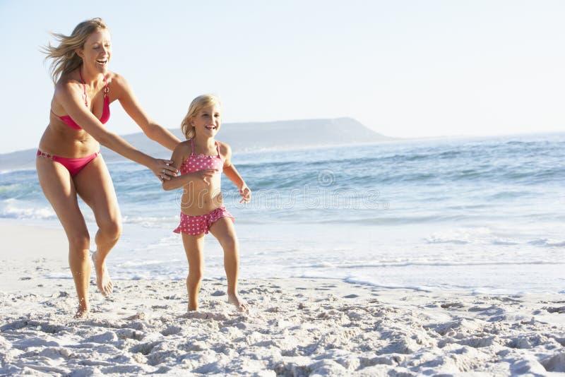 Mutter und Tochter, die entlang den Strand zusammen trägt Schwimmen-Kostüm läuft stockbild