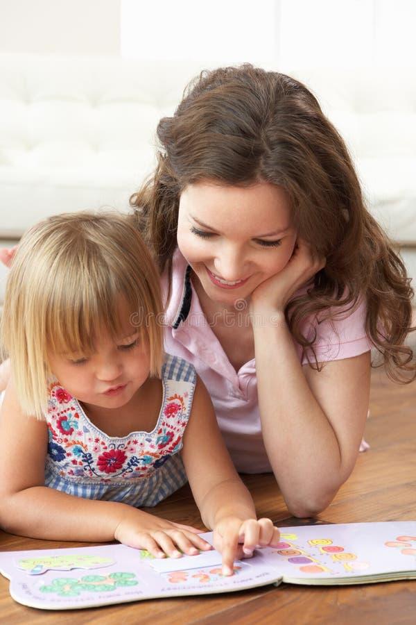 Mutter und Tochter, die erlernen, zu Hause zu lesen stockbilder