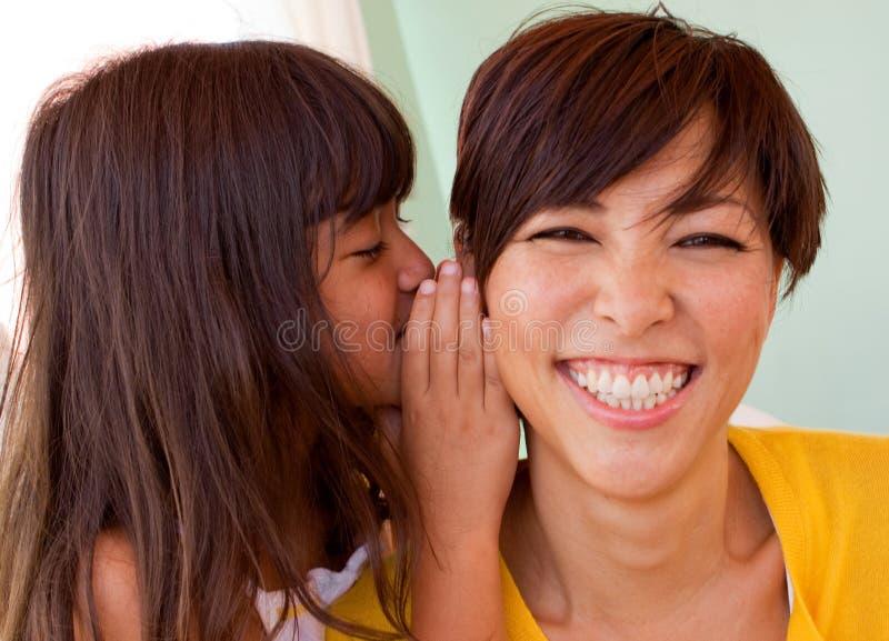 Mutter und Tochter, die Geheimnissen lächeln und sagen lizenzfreie stockfotografie