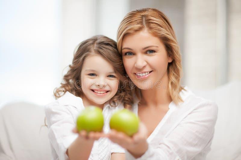 Mutter und Tochter, die grüne Äpfel halten lizenzfreies stockfoto