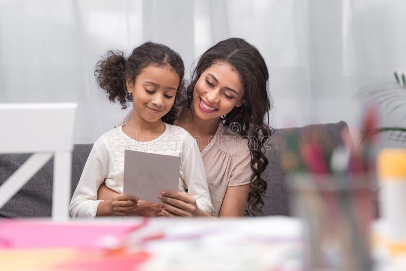 Mutter und Tochter, die Grußkarte am Muttertag betrachten stockfoto