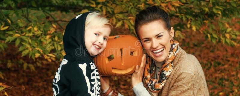 Mutter und Tochter, die Halloween-Kürbis Jack Oâ €™Lantern zeigt lizenzfreie stockfotografie