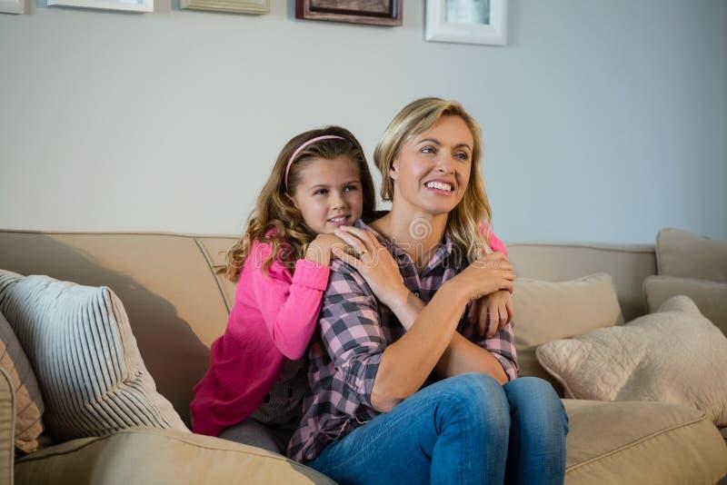 Mutter und Tochter, die im Wohnzimmer sich umfassen lizenzfreie stockfotos