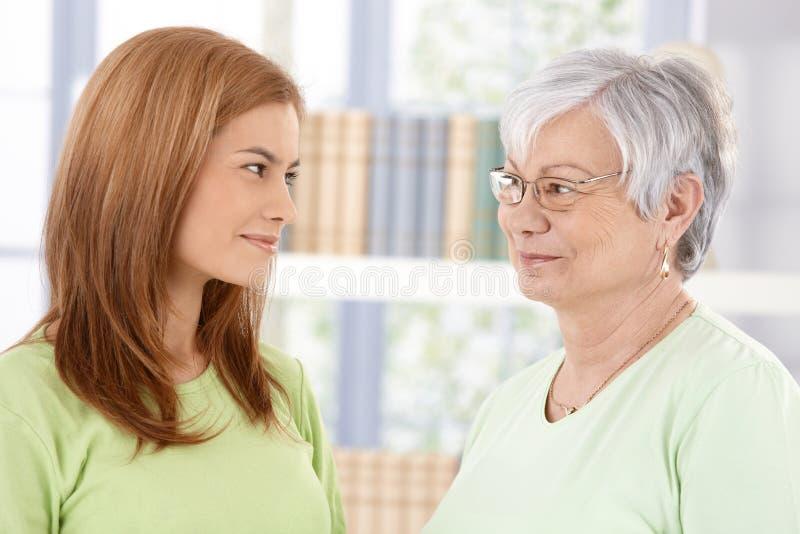Mutter und Tochter, die liebevoll lächeln stockbild