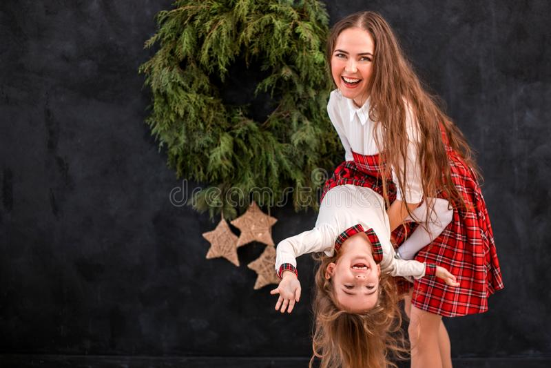 Mutter und Tochter, die nahe Weihnachtskranz spielen lizenzfreies stockfoto