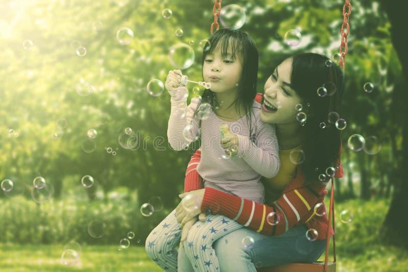 Mutter und Tochter, die Schlagseifenblasen des Spaßes am Park haben stockbilder