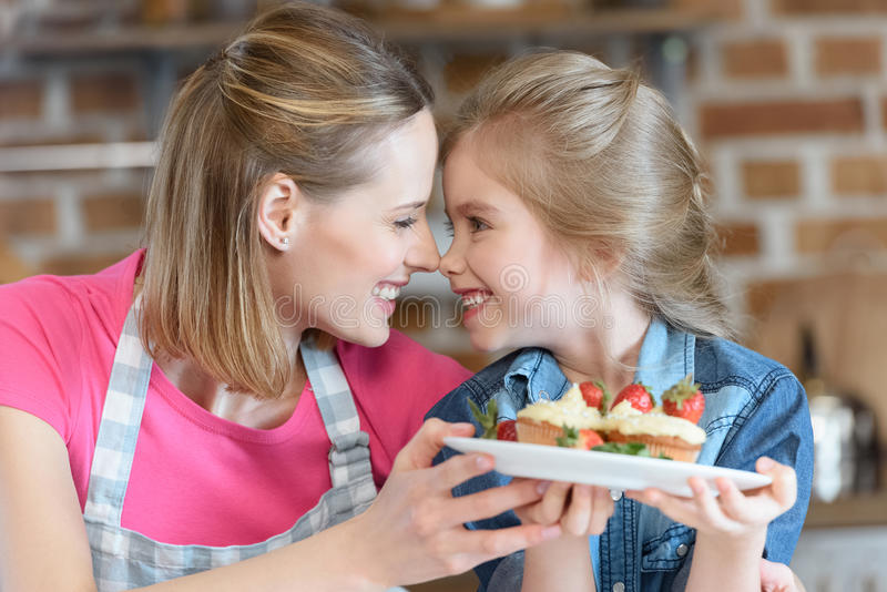 Mutter und Tochter, die selbst gemachte kleine Kuchen mit Erdbeeren halten lizenzfreies stockfoto
