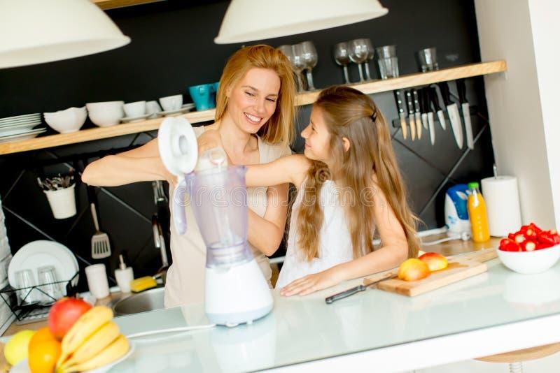 Mutter und Tochter, die shealthy Smoothie zubereiten lizenzfreie stockfotografie