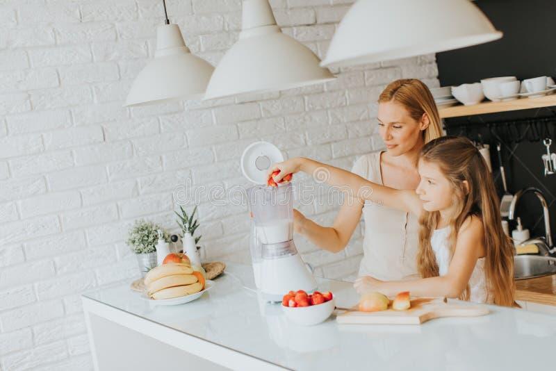 Mutter und Tochter, die shealthy Smoothie zubereiten lizenzfreies stockbild