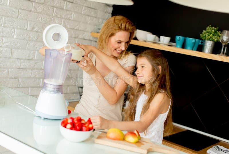 Mutter und Tochter, die shealthy Smoothie zubereiten lizenzfreie stockbilder