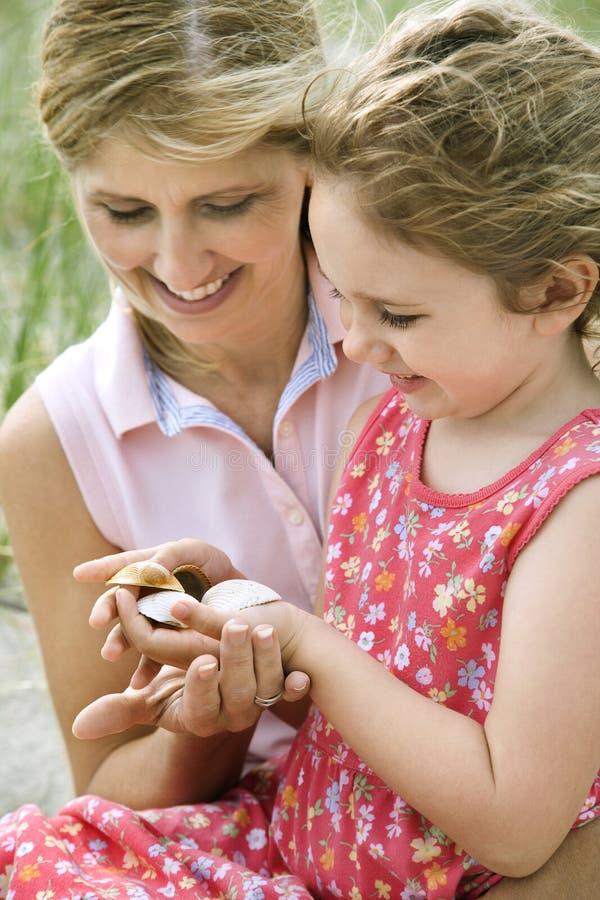 Mutter und Tochter, die Shells betrachten stockfotografie