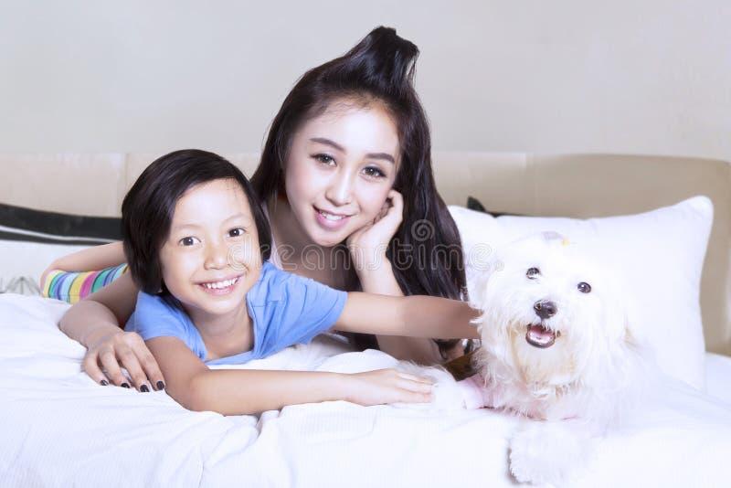 Mutter und Tochter, die sich zu Hause mit Welpen entspannen lizenzfreie stockfotos