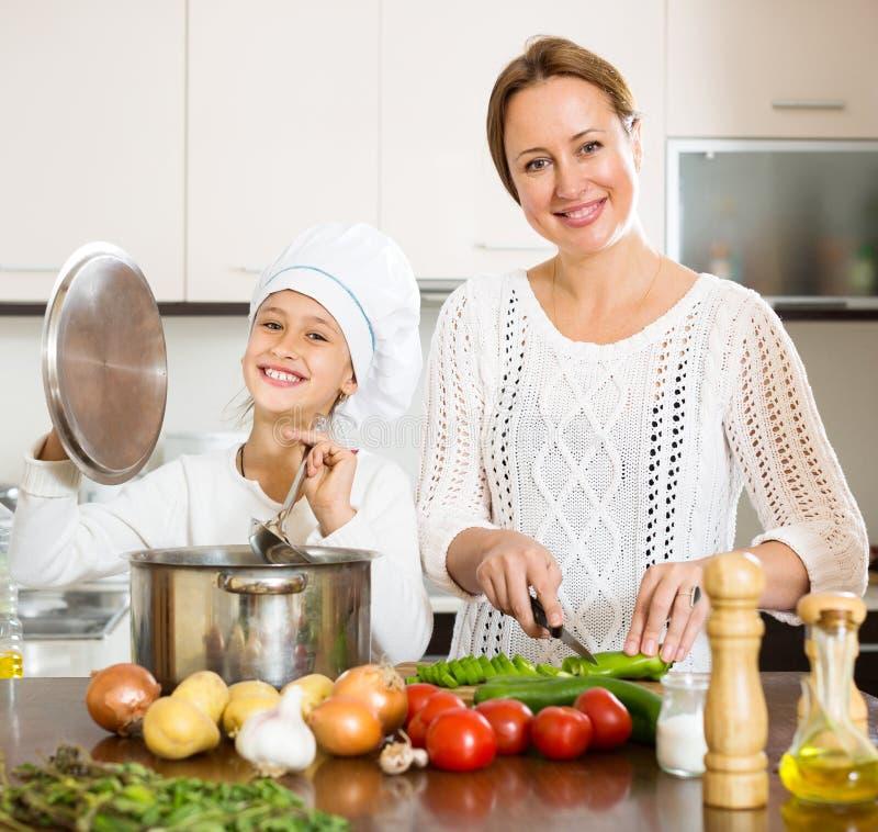 Mutter und Tochter, die Suppe zubereiten lizenzfreie stockbilder