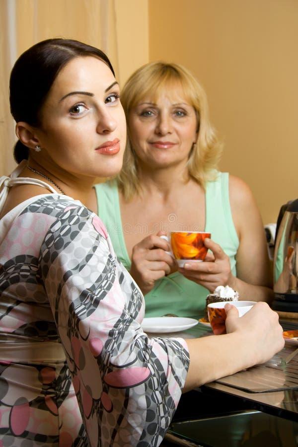 Mutter und Tochter, die t trinken stockbild