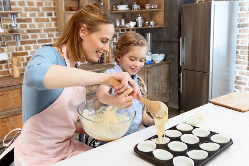 Mutter und Tochter, die Teig in Form für backende Plätzchen einsetzen lizenzfreie stockfotografie