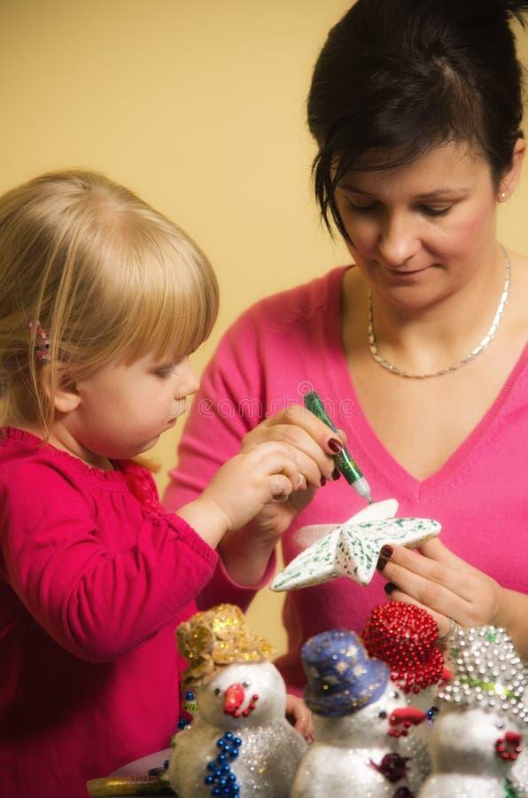 Mutter und Tochter, die Weihnachtsdekorationen machen stockfotos