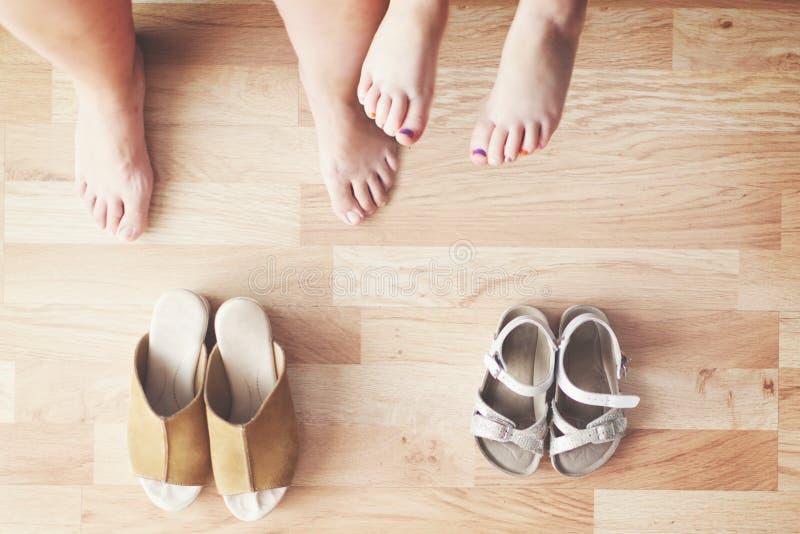 Mutter und Tochter, die zu Hause im Wohnzimmer sitzen Draufsicht von barfüßig Beinen und von Schuhen auf den barfüßigfüßen stockbilder