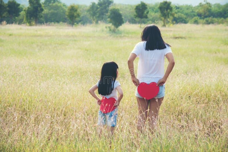 Mutter und Tochter, die zurück ein rotes Herz sie halten steht stockfoto