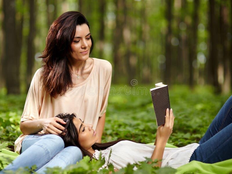 Mutter und Tochter, die zusammen ein Buch lesen stockbilder
