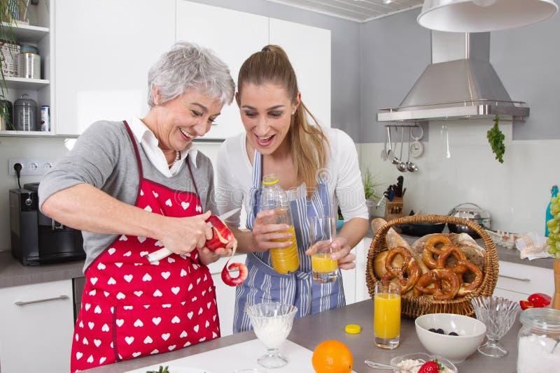 Mutter und Tochter, die zusammen Frühstück zubereiten stockfotografie