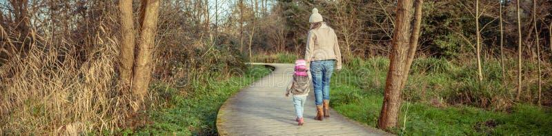 Mutter und Tochter, die zusammen Händchenhalten gehen lizenzfreie stockfotografie