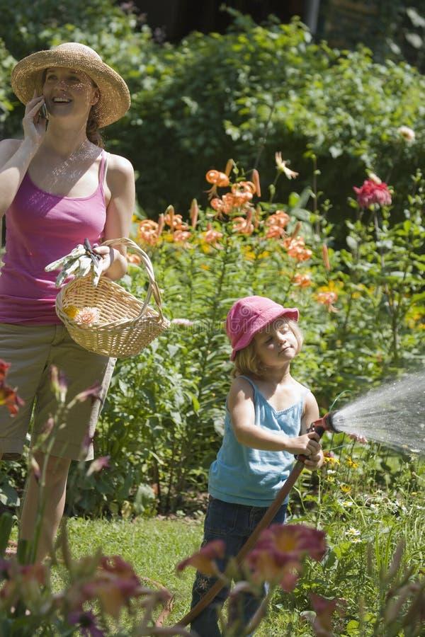 Mutter und Tochter, die zusammen im Garten arbeiten stockbild