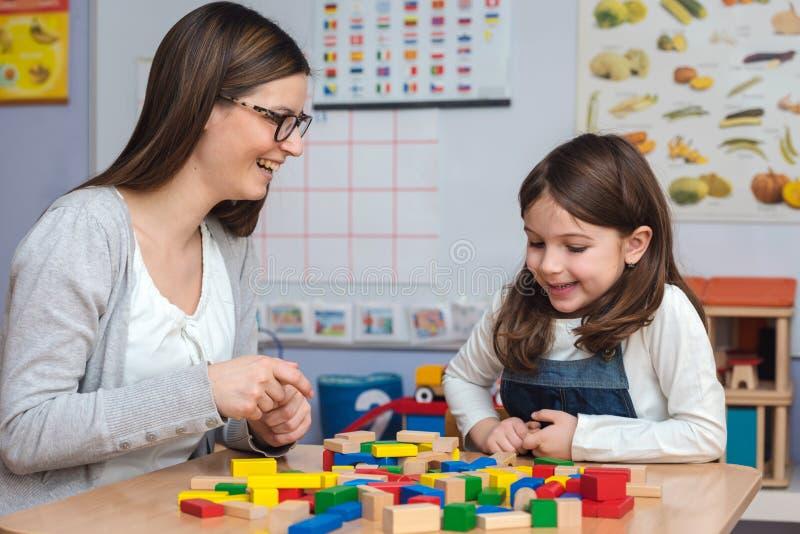 Mutter und Tochter, die zusammen mit bunten errichtenden Bauklötzen spielen lizenzfreies stockfoto