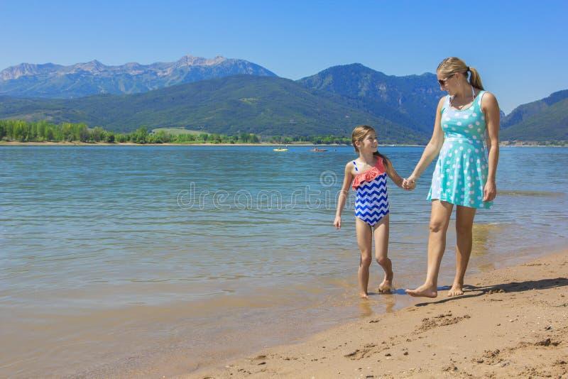 Mutter und Tochter, die zusammen am szenischen See gehen lizenzfreies stockbild
